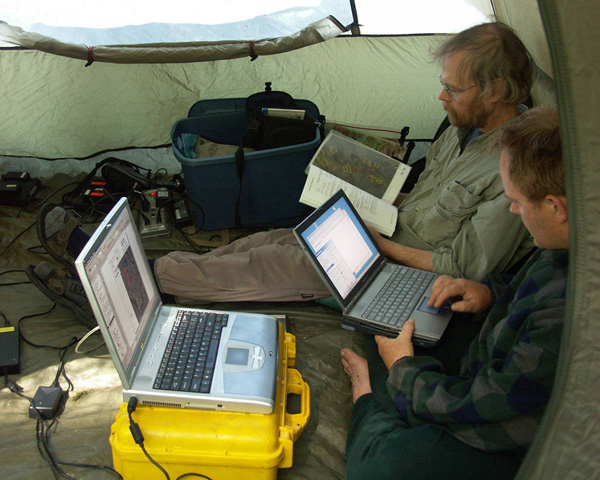 Office tent at Emerald Bay, June, 2005. Distant generator on long extension cord is powering 2 laptops and recharging batteries from cameras, GPS units and radios. Kenyon Fields photo.